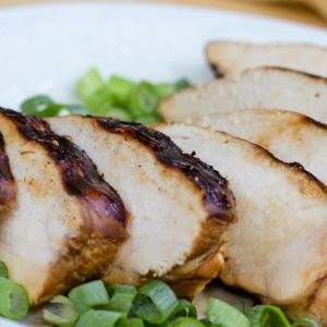 Sliced chicken breast on a white plate, garnished with chopped green onions.