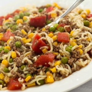 Ground beef, corn, peas, diced tomotoes, and ramen noodles on a white plate.