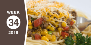 Image of spaghetti topped with a mixture of corn, diced tomatoes, green onions, ground beef, and garnished with shredded cheese on top; text Week 34 2019