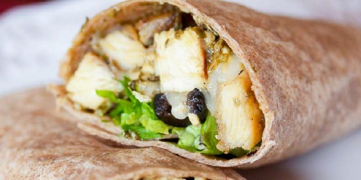Diced chicken, sliced black olives, lettuce, and pesto wrapped in a tortilla. The wrap is on top of another similar wrap, next to some pesto on a white plate.