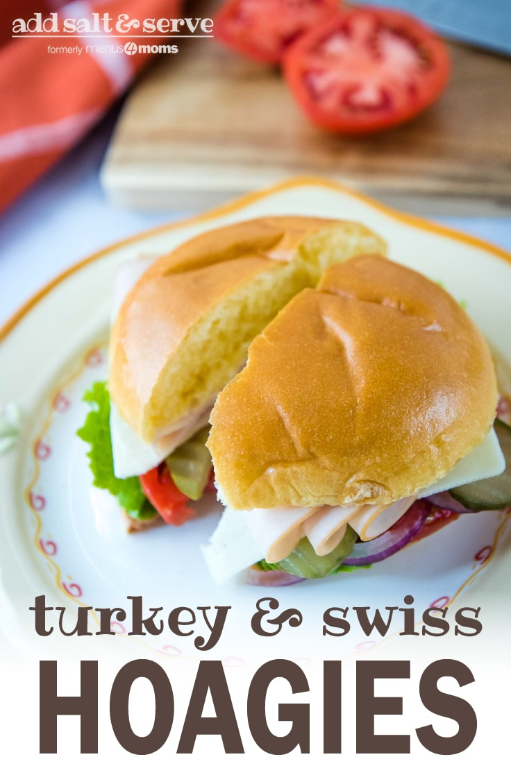 Brioche bun with slices of turkey, Swiss cheese, lettuce, tomato, pickle, and onion on a white and orange plate with cutting board and tomato in the background; text Turkey & Swiss Hoagies Add Salt & Serve (formerly Menus4Moms)