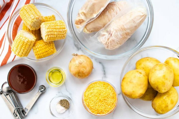 Clear glass bowl with small corn on the cob, clear glass bowl with individually wrapped chicken breasts, clear glass bowl of whole, unpeeled potatoes, bowl of shredded cheddar cheese, bowl with salt and pepper, metal measuring spoons, bowl of barbecue sauce, bowl of oil, and an onion, all on a white marble countertop with an orange and white striped napkin.