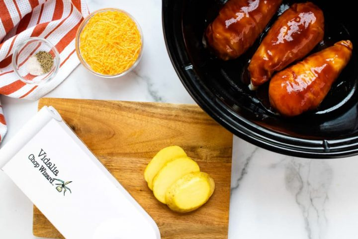 Small bowl with salt and pepper sitting on an orange and white striped napkin, a bowl of shredded cheddar cheese, a slow cooker with three chicken breasts in barbecue sauce, a wooden cutting board with sliced potatoes, and a Vidalia Chop Wizard.