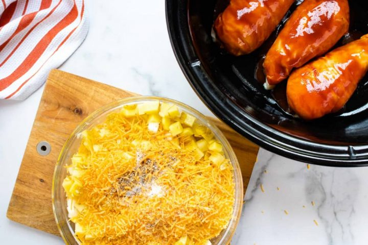 An orange and white striped linen napkin on a white marble countertop with a slow cooker with three chicken breasts in barbecue sauce. A wooden cutting board with a bowl of diced potatoes and onions, shredded cheddar cheese, and salt and pepper.