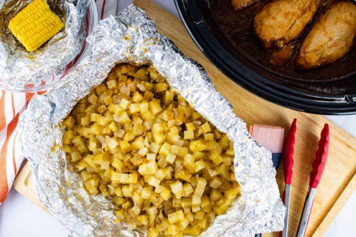 A bowl with foil and a small corn cob, open foil packet with diced potatoes, a slow cooker with chicken breasts. The potatoes are on a wooden cutting board with a basting brush and a set of tongs.