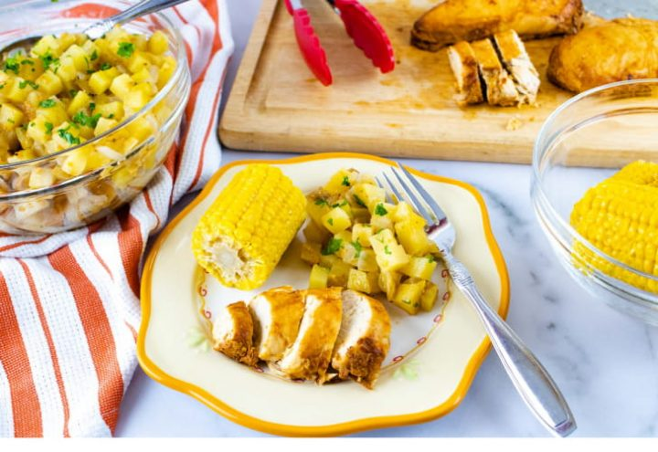 Photo is a clear glass bowl of diced potatoes sitting on an orange and white striped linen napkinn, a wooden cutting board with tongs and sliced chicken, a clear glass bowl of corn on the cob, and a plate with a small corn cob, diced potatoes, and sliced chicken. The plate is off-white with a yellow rim. There is a fork on the plate beside the potatoes.