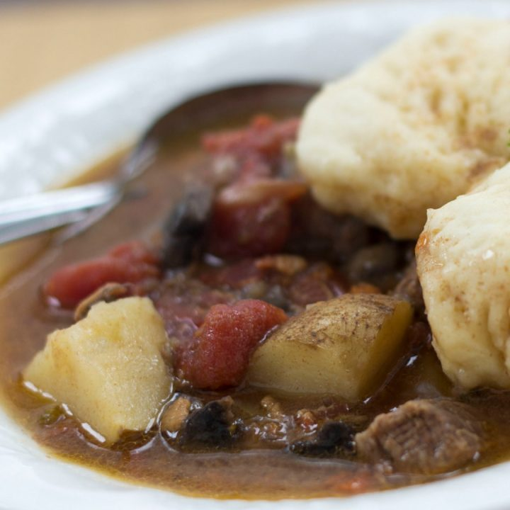 White bowl of beef stew with two dumplings on top. Stew consists of brown broth, diced beef, chopped potatoes, and stewed tomatoes. There is a spoon in the bowl on the left side.