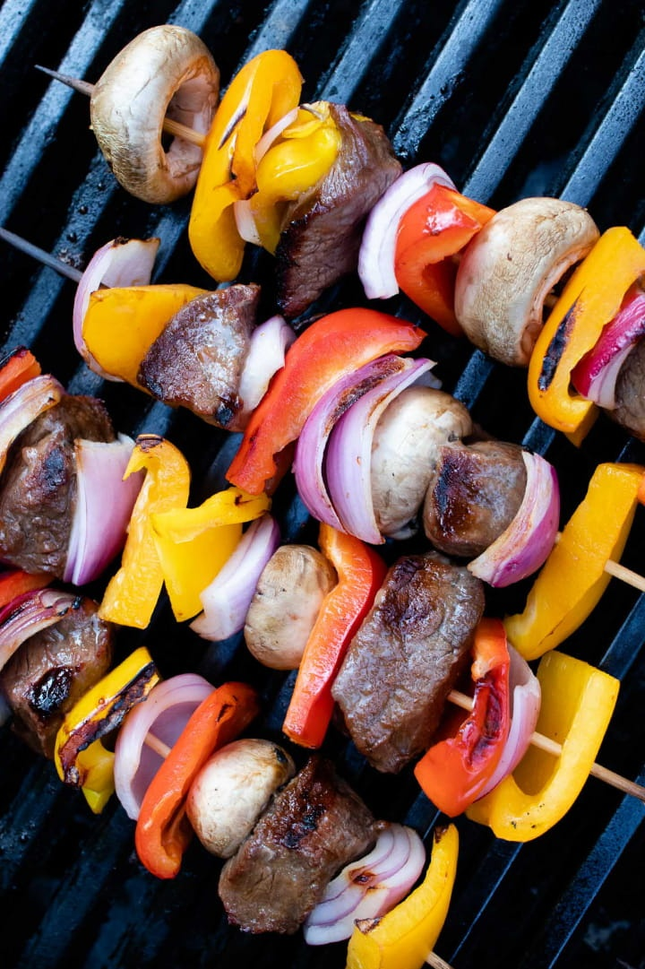 kabobs of red, yellow, and orange bell pepper pieces alternated with mushrooms, red onion pieces, and marinated beef on a grill