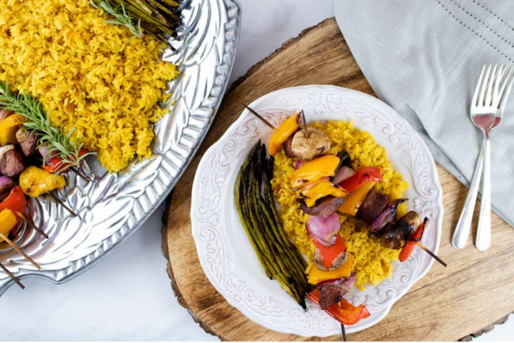 grilled kabobs of red, yellow, and orange bell pepper pieces alternated with mushrooms, red onion pieces, and marinated beef and layered over yellow rice with grilled asparagus on a white plate with a silver fork with a serving platter of kabobs, yellow rice, and asparagus to the side