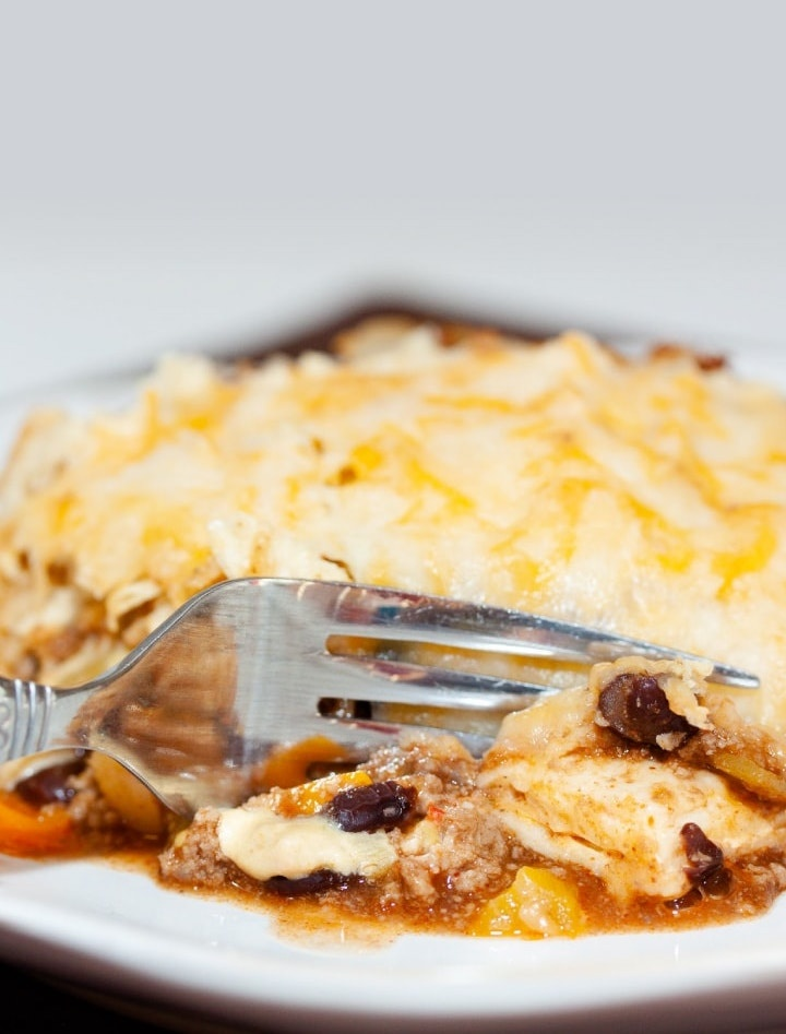 A tortilla covered with melted cheese, on top of ground beef, black beans, and tomatoes, all on a white plate. A fork is cutting into the tortilla.