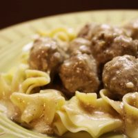 Yellow bowl with egg noodles covered in meatballs with cream sauce