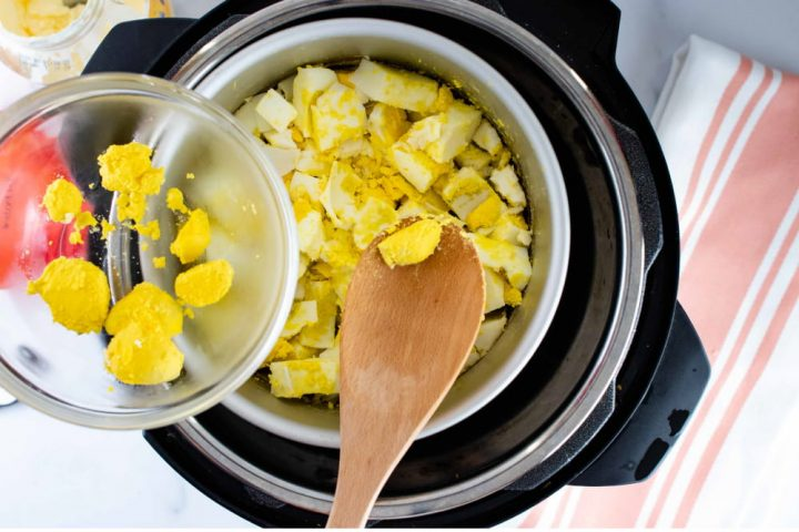 Overhead view of a layer of cooked eggs in an inner pot in an Instant Pot cut into squares with a wooden spoon pulling out some of the cooked yolk