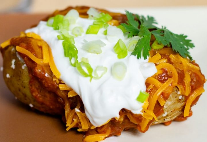 Baked potato topped with chili, shredded cheddar cheese, sour cream, and diced green onions.