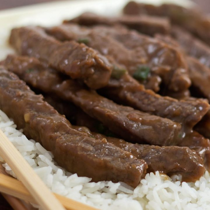 Sliced steak with a sauce on a bed of rice with chopsticks in the foreground.