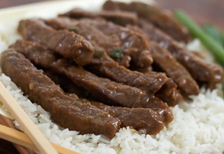 Sliced steak with a sauce on a bed of rice with scallions in the background and chopsticks in the foreground.