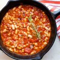 Cast iron skillet with Pasta e Fagioli, a soup made with pasta,tomatoes, chopped celery and onion, cannellini beans, and tomato sauce.