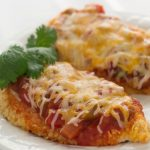 Two chicken breasts coated with cracker crumbs, and topped with salsa and melted shredded cheese, on a white plate.