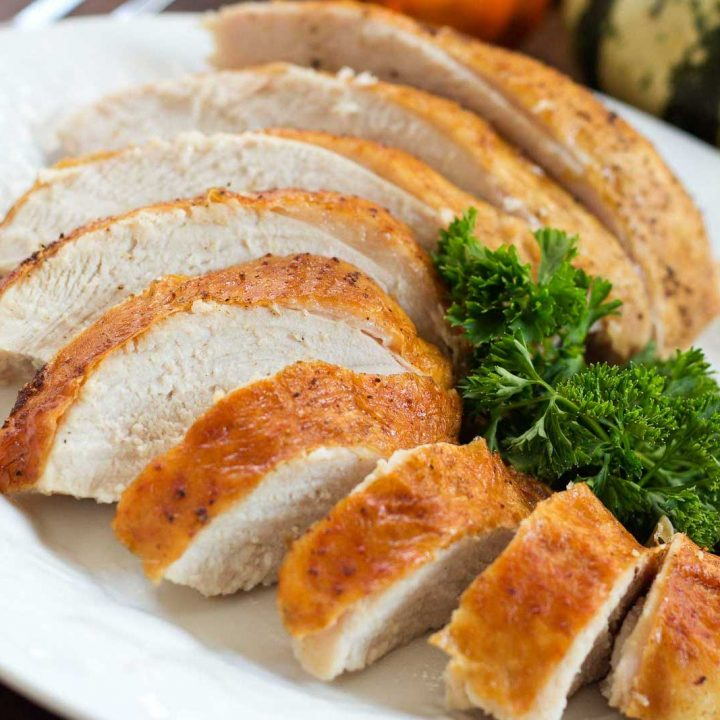 Sliced roasted turkey breast with golden brown skin on a white plate garnished with parsley