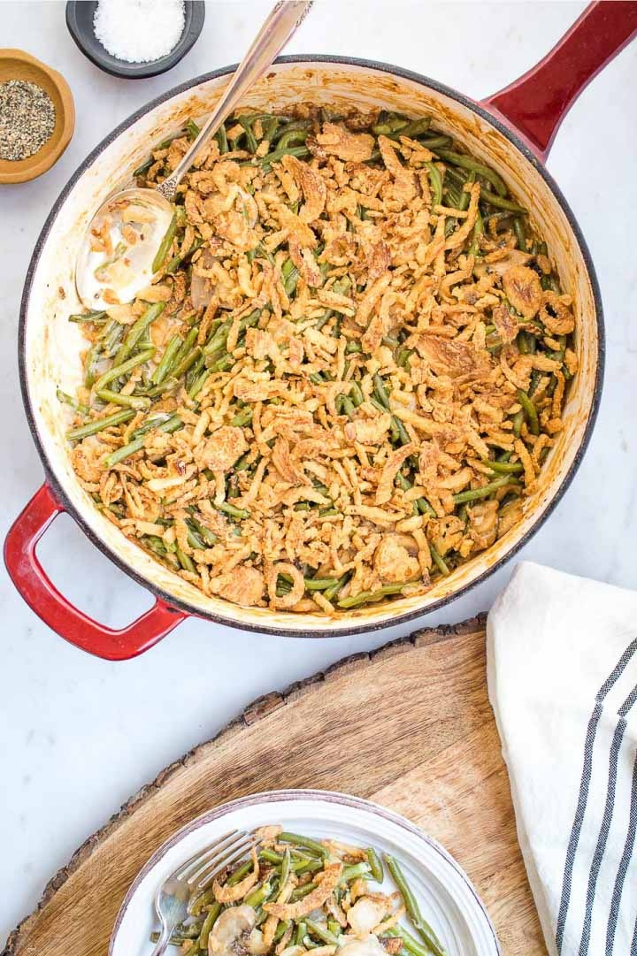 Skillet with green bean casserole topped with crunchy fried onions and a plate with a serving of green bean casserole to the side.