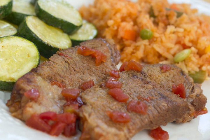 A white plate with sliced cucumbers, two slices of pot roast garnished with diced tomatoes, and Mexican Style Rice.