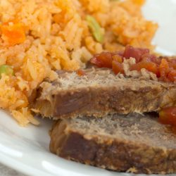 Mexican style rice on a plate with two slices of roast beef and diced tomatoes