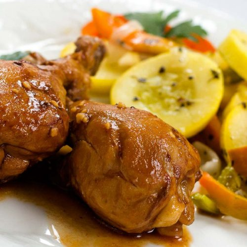 Two chicken drumsticks on a white plate with sliced yellow squash, onions, and bell peppers.
