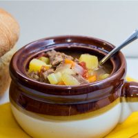 Brown and white soup bowl with vegetable beef soup and a spoon, next to a loaf of bread.