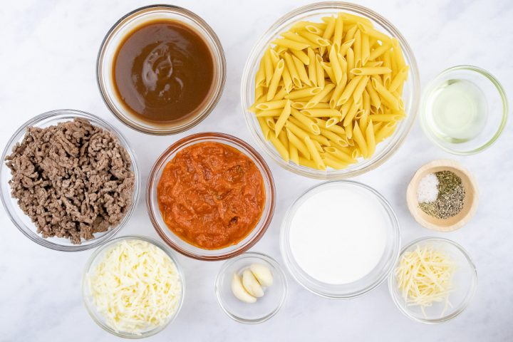 Overhead view of ingredients for Penne Pasta Bake: penne pasta, cooked ground beef, spaghetti sauce, brown gravy, garlic, half and half, mozzarella cheese, parmesan cheese, herbs, salt & pepper