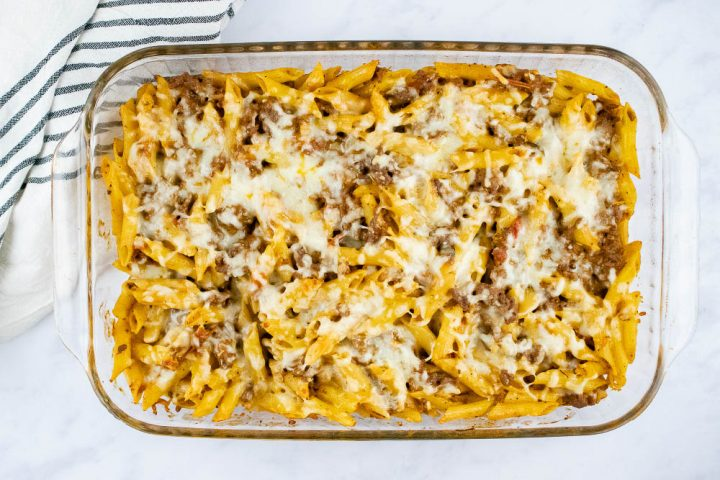 Overhead view of baked penne pasta bake topped with shredded cheese in a glass pan