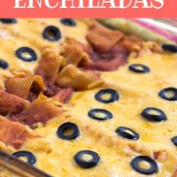 Glass casserole dish with enchiladas topped with melted cheese and sliced black olives. Text Ground Beef Enchiladas Add Salt & Serve formerly Menus4Moms
