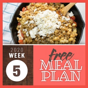 Overhead view of a cast iron skillet with pasta, chicken, bell peppers, and crumbled feta cheese being stirred with a wooden spoon and text Week 5 free meal plan