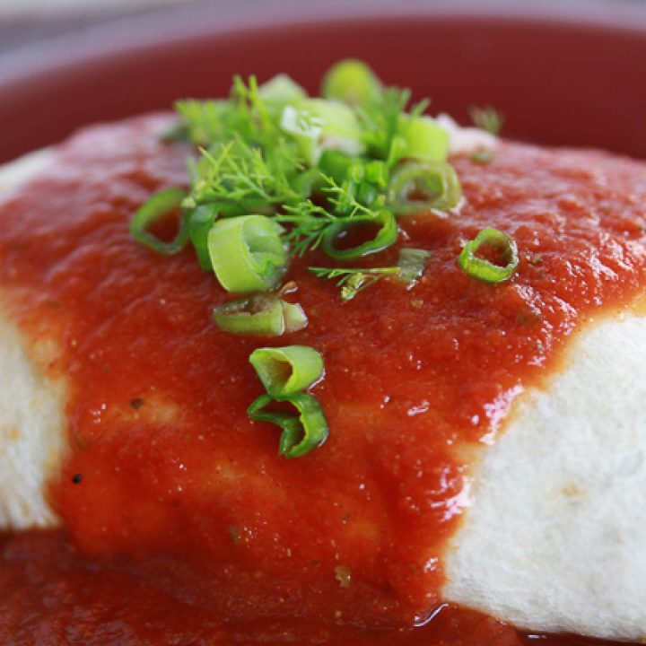 Burrito with red sauce poured over it and garnished with cilantro and chopped green onions