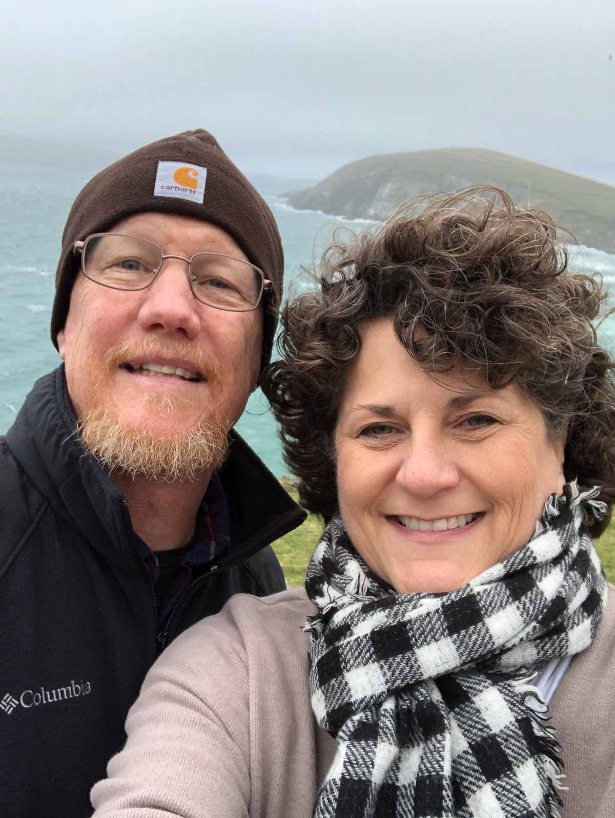 Man and woman in winter clothing facing camera with atlantic ocean and peninsula in background