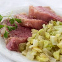 Corned beef and cabbage on a white plate garnished with a sprig of parsley.