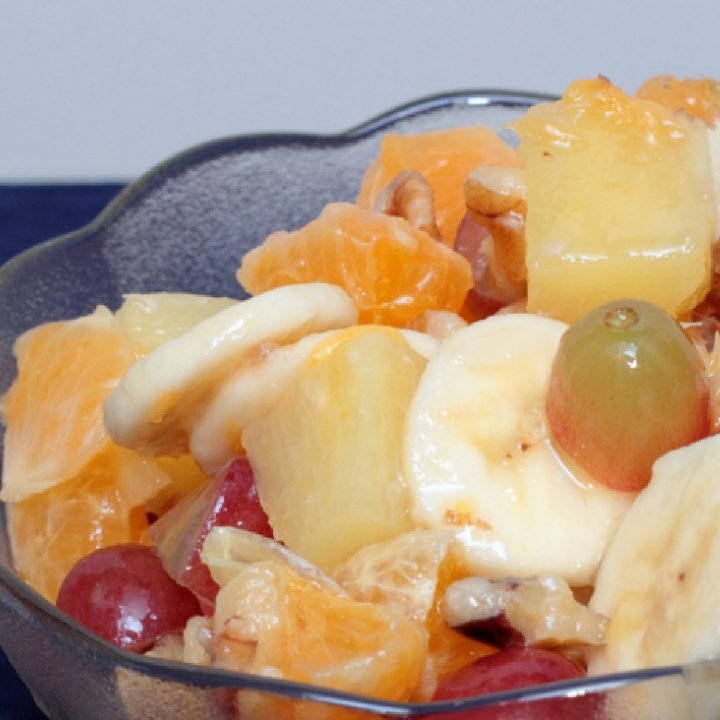 Grapes, chopped oranges, pineapples, and walnuts, and sliced bananas in a bowl.