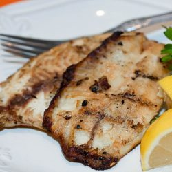 White plate with fish fillets garnished with lemon wedges and parsley