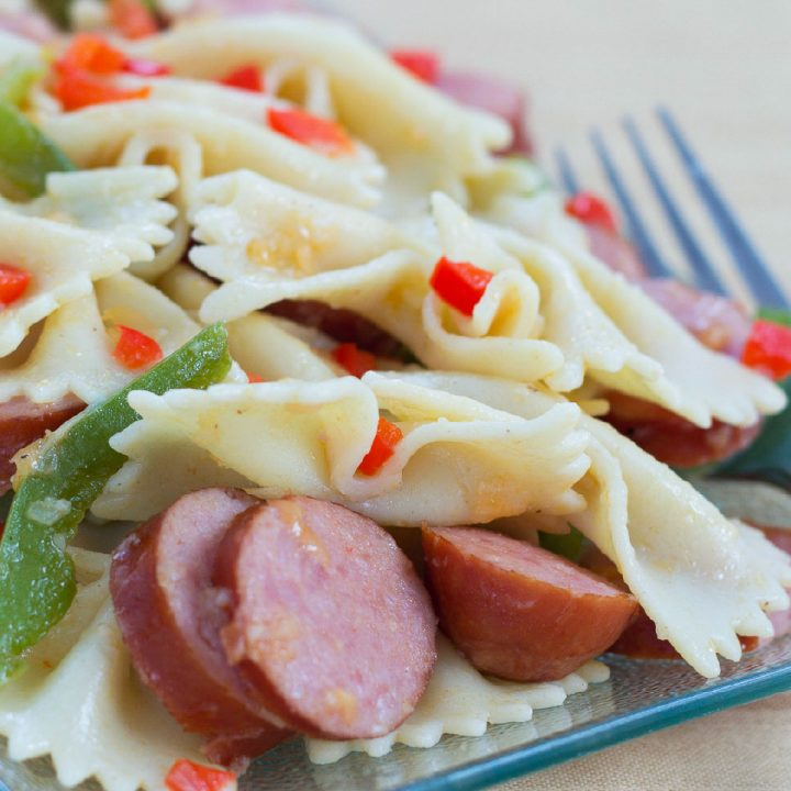 A plate of sliced bell peppers and sausauge and bow-tie pasta