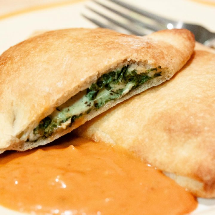 Spinach calzones on a plate with spaghetti sauce