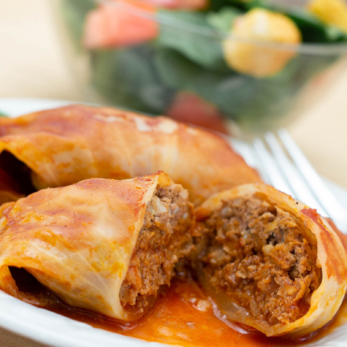Closeup of cabbage rolls in a tomato sauce on a white plate with a fork. Bowl of salad in the background.