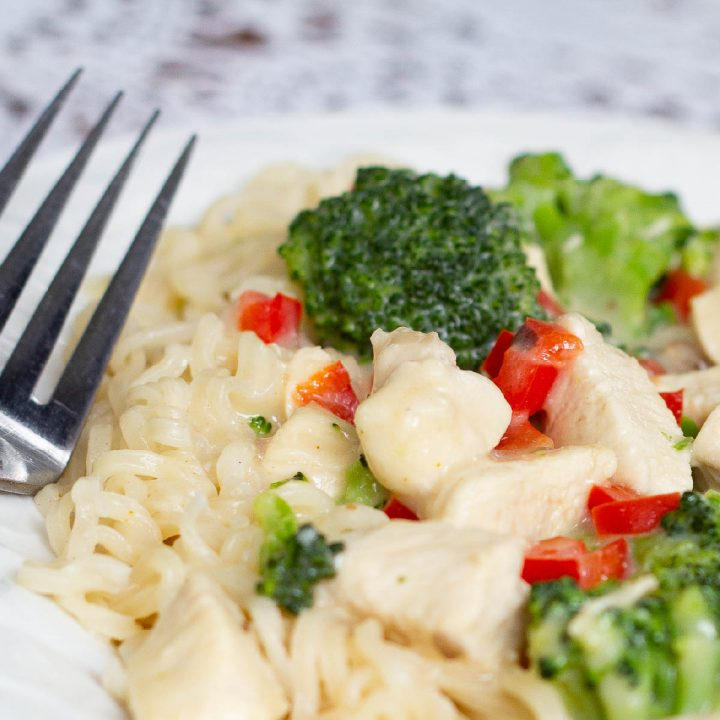 A plate with Creamy Chicken and Broccoli Ramen and a fork.