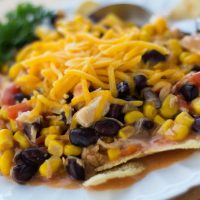 Corn and black beans topped with shredded cheddar cheese on a bed of tortilla chips on a white plate