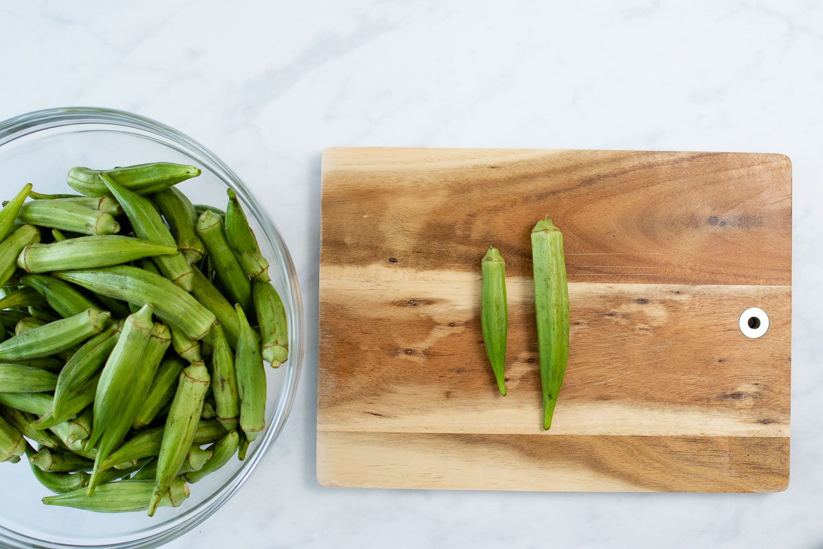 A bowl of okra and okra on a cutting board