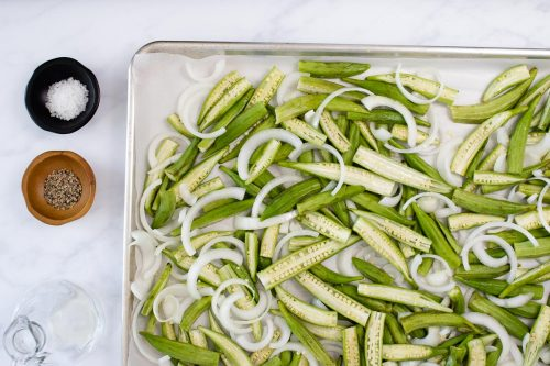 Chopped okra and onion on a baking sheet, nearby are bowls of oil, salt, and pepper