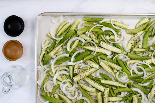 Chopped okra and onion on a baking sheet, nearby are empty bowls and an empty carafe