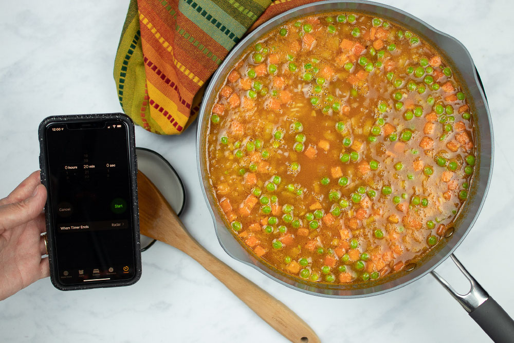 In-process Restaurant Style Mexican Rice in a skillet, and a hand holding a phone using the timer