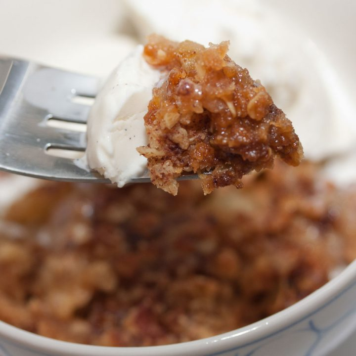 A fork picking up a bite of Apple Crumble topped with ice cream.
