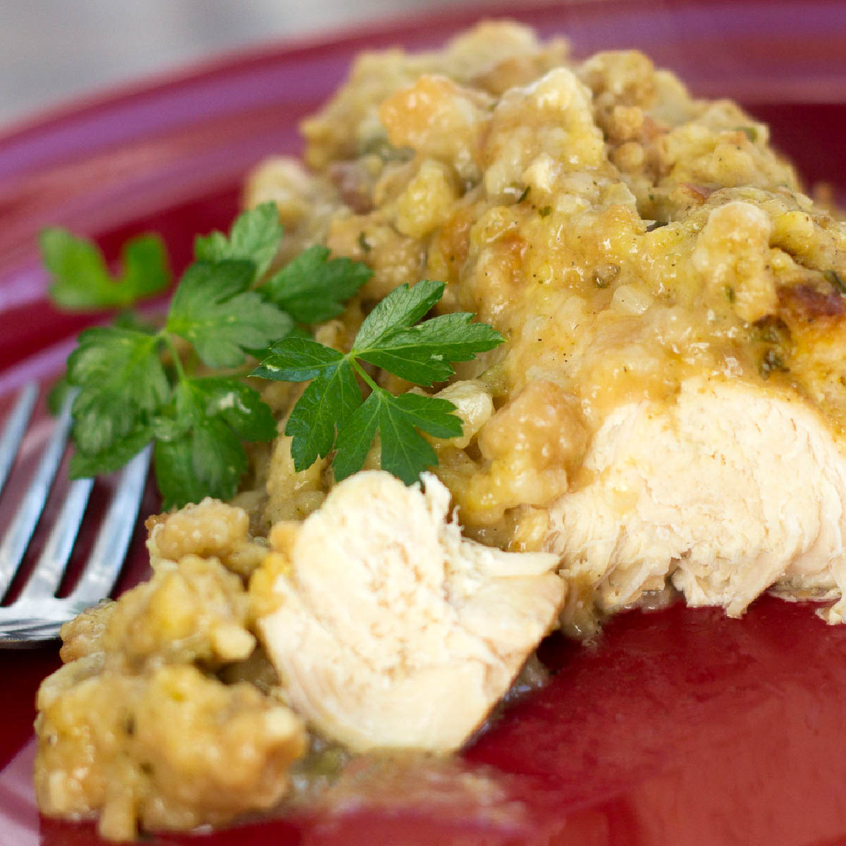 A chicken breast topped with gravy and stuffing on a plate with a fork.
