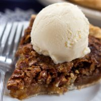 Homemade pecan pie topped with a scoop of vanilla ice cream