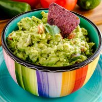Homemade guacamole in a rainbow-striped bowl, with half an avocado in the background.