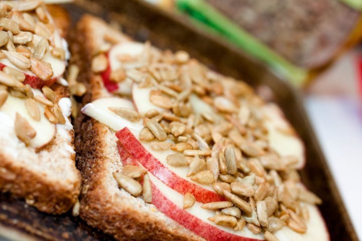 toast spread with mayo, apple slices, and sunflower seeds and text Add Salt & Serve